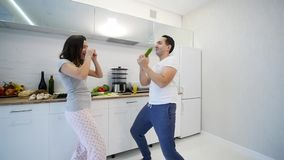 Coppie felici di mattina a casa le giovani recentemente wed il dancing che ascolta la musica in pigiami d'uso della cucina Movime archivi video