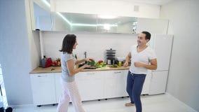Coppie felici di mattina a casa le giovani recentemente wed il dancing che ascolta la musica in pigiami d'uso della cucina Movime stock footage