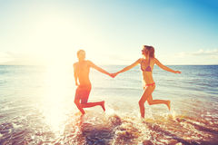 Coppie felici di tramonto alla spiaggia Immagini Stock Libere da Diritti