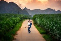 Coppie felici divertendosi nel campo al tramonto fotografia stock libera da diritti