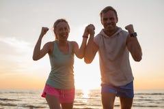 Coppie felici dopo l'allenamento sulla spiaggia Immagini Stock