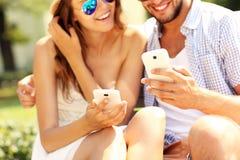 Coppie felici facendo uso degli smartphones Fotografia Stock Libera da Diritti