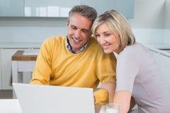 Coppie felici facendo uso del computer portatile in cucina fotografia stock