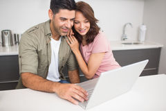 Coppie felici facendo uso del computer portatile in cucina Fotografie Stock Libere da Diritti