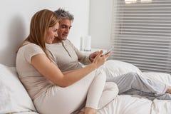 Coppie felici facendo uso del ipad nel letto Immagini Stock
