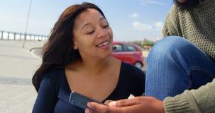 Coppie felici facendo uso del telefono cellulare sul banco 4k video d archivio