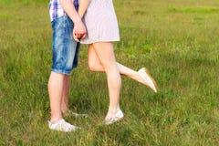 Coppie felici giovani che baciano nell'amore, stante sull'erba nel sole di estate la notte Fotografie Stock