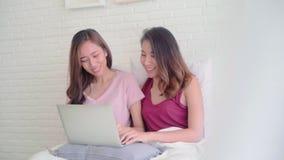 Coppie felici lesbiche delle giovani donne asiatiche facendo uso del computer portatile del computer che controlla media sociali  stock footage