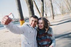 Coppie felici nell'amore che abbraccia e che divide le emozioni, tenendosi per mano camminata nel parco e fabbricazione dei selfi Fotografia Stock