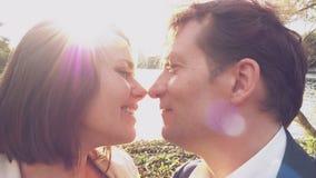 Coppie felici nell'amore che bacia davanti al lago al movimento lento di tramonto archivi video