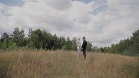 Coppie felici nell'amore che sta sul tenersi per mano del campo stock footage