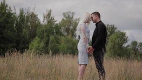 Coppie felici nell'amore che sta sul tenersi per mano del campo video d archivio