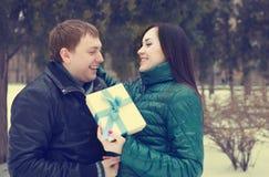 Coppie felici nell'amore con divertiresi attuale nel parco di inverno Fotografia Stock Libera da Diritti