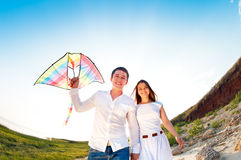 Coppie felici nell'amore con pilotare un aquilone sulla spiaggia Fotografia Stock