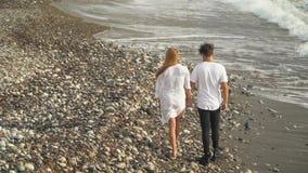 Coppie felici nella passeggiata bianca del vestito lungo tenersi per mano roccioso della spiaggia Svago di giovane famiglia Fucil video d archivio