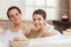 Coppie felici nella vasca della stazione termale immagini stock