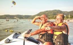 Coppie felici senior divertendosi sul jet ski alla luppolizzazione di isola della spiaggia immagini stock libere da diritti