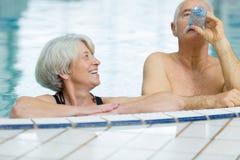 Coppie felici senior nella piscina fotografie stock