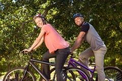 Coppie felici su un giro della bici Immagini Stock Libere da Diritti