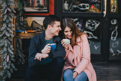 Coppie felici in vestiti caldi che bevono caffè su un mercato di Natale Immagini Stock Libere da Diritti