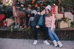 Coppie felici in vestiti caldi che posano su un mercato di Natale Immagini Stock