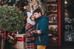 Coppie felici in vestiti caldi che posano su un mercato di Natale Immagine Stock
