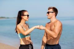 Coppie felici in vestiti di sport e tonalità sulla spiaggia Fotografia Stock Libera da Diritti
