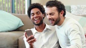 Coppie gay che si rilassano sullo strato che prende selfie video d archivio