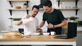 Coppie gay felici che preparano prima colazione in cucina alla mattina Bello un giovane gay che mette i cereali da prima colazion archivi video