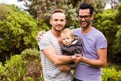 Coppie gay sorridenti con il bambino fotografia stock