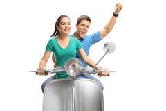Coppie giovani allegre che guidano un motorino d'annata immagine stock libera da diritti