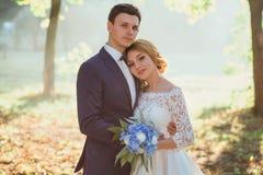 Coppie giovani attraenti di stupore nel giorno delle nozze sposa in vestito lungo bianco elegante ed in mazzo blu a disposizione, fotografie stock libere da diritti