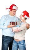 Coppie giovani in cappelli della Santa che tengono i contenitori di regalo Immagine Stock Libera da Diritti