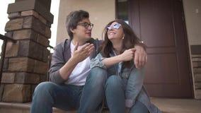 Coppie giovani di risata che si siedono insieme sul sulla loro portico e conversazione della casa video d archivio