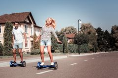 Coppie giovani felici divertendosi guida sui motorini di equilibrio fotografia stock