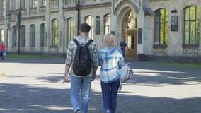 Coppie gli studenti che camminano all'accademia e che discutono esame futuro, rallentatore archivi video