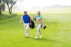 Coppie Golfing che camminano sul verde mettente Immagini Stock Libere da Diritti