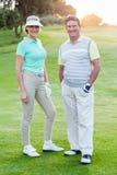 Coppie Golfing che sorridono alla macchina fotografica sul verde mettente Fotografia Stock Libera da Diritti