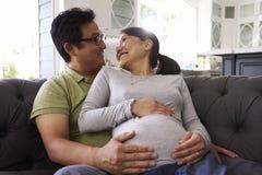 Coppie in grande aspettativa che si rilassano su Sofa At Home Together immagine stock
