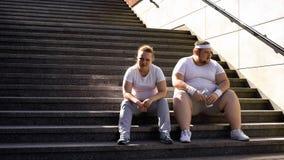 Coppie grasse che si siedono sulle scale, esaurite dopo gli addestramenti fisici, unità immagine stock libera da diritti
