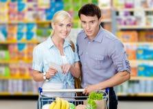 Coppie graziose che discutono la lista di acquisto ed i prodotti scelti fotografie stock