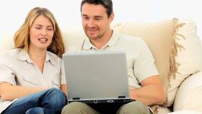 Coppie graziose facendo uso di un computer portatile stock footage