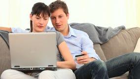 Coppie graziose facendo uso di una carta di credito su Internet archivi video