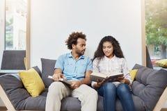 Coppie i bei giovani studenti neri che si siedono nella biblioteca dopo lo studio, leggenti informazioni su storia antica Immagini Stock Libere da Diritti