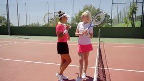 Coppie i tennis svegli che posano vicino alla rete video d archivio