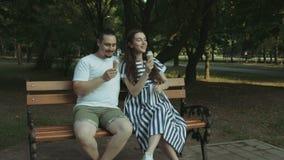 Coppie incinte allegre che mangiano il gelato in parco archivi video
