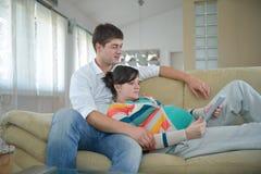 Coppie incinte a casa facendo uso del computer della compressa Fotografie Stock