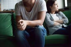 Coppie infelici che si siedono sullo strato a casa fotografia stock