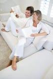 Coppie insieme sulla lettura e sulla chiacchierata del sofà fotografie stock