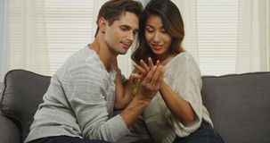 Coppie interrazziali che esaminano anello di fidanzamento Fotografia Stock
